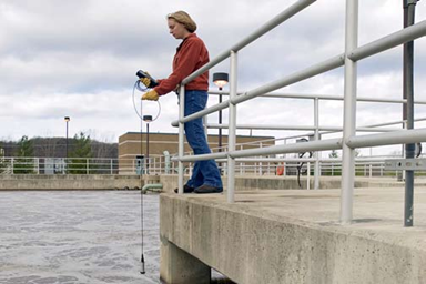 Scientist monitoring temperature, dissolved oxygen, and pH with the YSI YSI Professional Series.