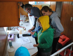 Students below deck on the Boat of Knowledge testing water quality parameters.