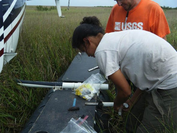 Khan and a U.S. Geological Survey collaborator measure a sediment sample from the wetland.