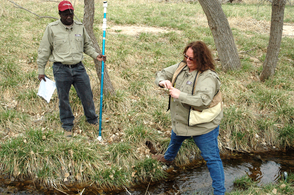 Phyllis Dyer takes a sample from Buck Creek as fellow associate, Partson Muvumba, looks on (Credit: Texas A&M AgriLife Research, Kay Ledbetter)