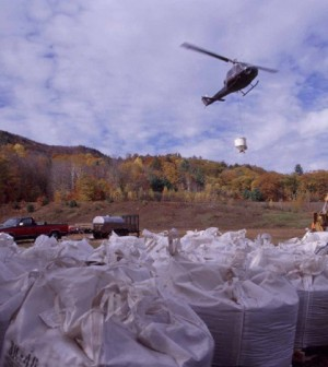 A helicopter loaded with calcium fertilzer pellets takes off over the Hubbard Brook Experimental Forest (Credit: Hubbard Brook Ecosystem Study)