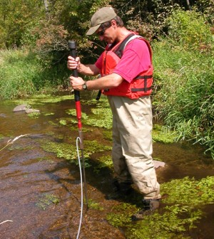Jim Tesoriero installs a piezometer to sample groundwater in the Tomorrow River streambed. (Credit: USGS)