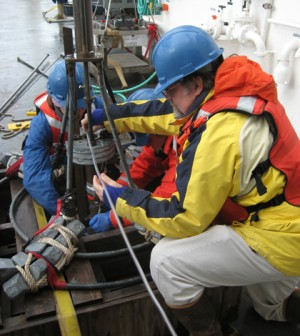 WHOI researcher Bruce Keafer, right, and colleagues prepare a corer to collect sediment samples from the seafloor. (Credit: Amy Lloyd-Rippe)