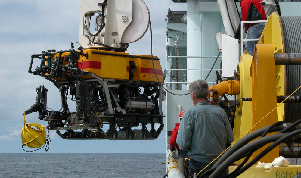 The remotely operated vehicle ROPOS being recovered by the R/V Thomas G. Thompson with a short period seismometer package developed by the Monterey Bay Aquarium Research Institute held by the manipulator arm.  (Credit: Mitchell Elend, UW)