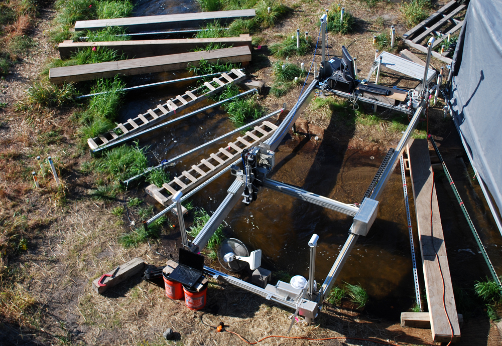 An overview of the experimental setup at the Outdoor StreamLab, including the mechanized cart supporting the acoustic Doppler velocimeter and spectrometer (Credit: Carl Legleiter)