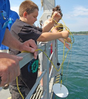 Students learn about secchi disks on a New Hampshire Sea Grant Discovery Cruise (Credit: New Hampshire Sea Grant, via Flickr)