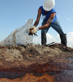 Worker cleans up debris from the Deepwater Horizon oil spill (Credit: Patrick Kelley, Wikimedia Commons)