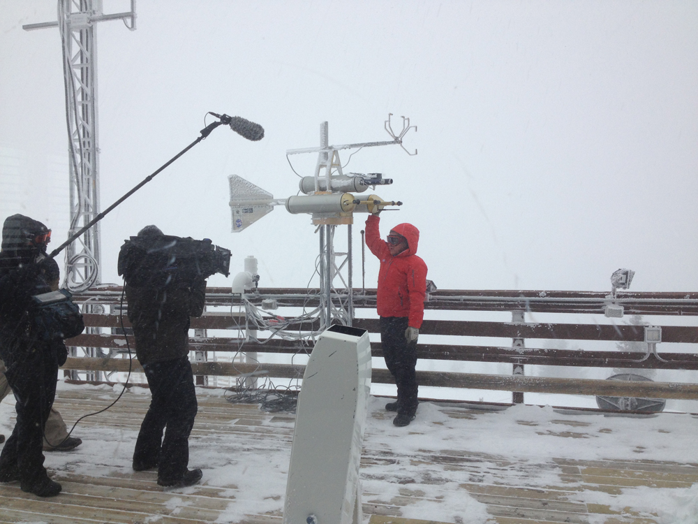Storm Peak Site Manager Ian McCubbin, shows off some of the lab's instruments for a Weather Channel camera crew (Credit: Storm Peak Laboratory)