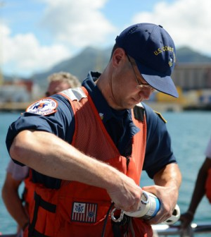Coast Guard Petty Officer 1st Class James Moore prepares a water quality instrument used to monitor depleted oxygen and pH levels in the Honolulu Harbor (Credit: Coast Guard News, via Flickr)