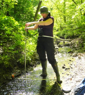 Michaeleen Gerken Golay measures stream flow in a forested headwater stream