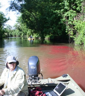 Monitoring boat in the channel of Ninemile Creek, downstream of the dye release location. (Credit: Upstate Freshwater Institute)