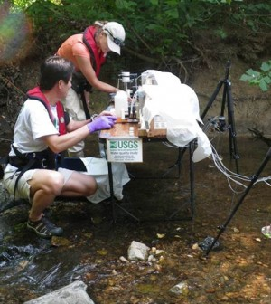 U.S. Geological Survey scientists sample water and sediment in Accotink Creek near Ranger Road in the City of Fairfax, Va. (Credit: Jud Harvey)