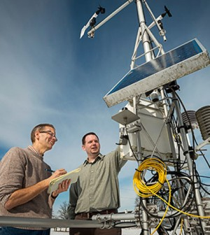 Inspecting a Delaware Environmental Observing System weather station. (Credit: University of Delaware)