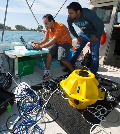 Electrical engineering graduate students Hovannes Kulhandjian and Zahed Hossain in the lab boat of Tommaso Melodiaís WINES Lab Research on Lake Erie (Credit: Douglas Levere)