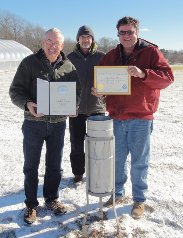 Olsen (left) with the rain can and National Weather Service award (Credit: National Weather Service)