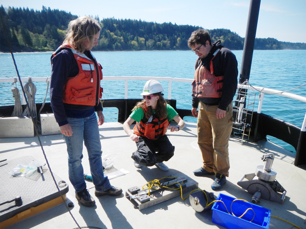 Students and faculty discuss the deployment of a short term mooring to study the attenuation of light reaching the seabed due to sediment in the Elwha River plume. (Credit: Emily Eidam)