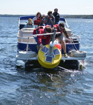"A crew launches ""Goldie,"" the Great Pond data buoy (Credit: Colby College)"
