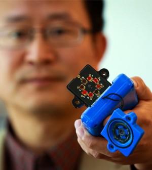 Professor Ling Zang holds a prototype detector. (Credit: Dan Hixon)