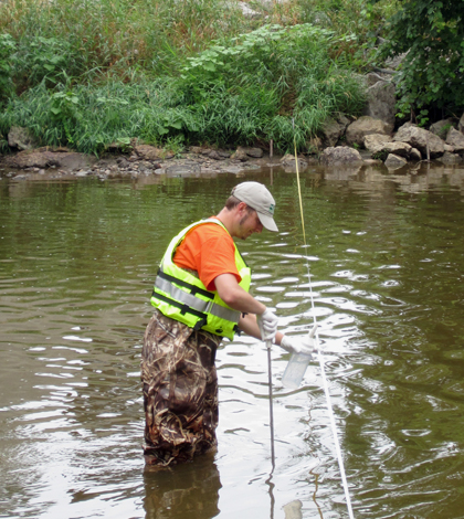 Pete Lenaker of the USGS collects a water sample from the Manitowoc River near Manitowoc, WI. (Credit: USGS)