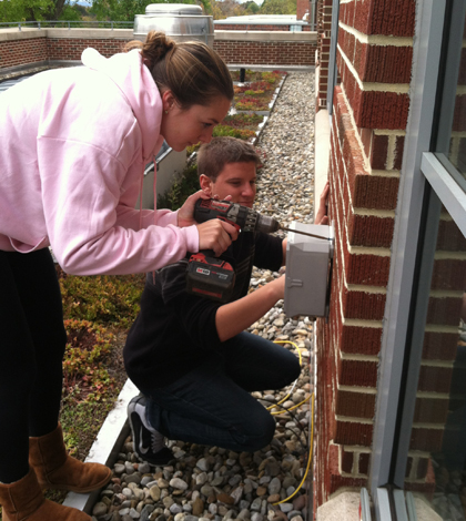 Muhlenberg College students install a junction box for the green roof monitoring system. (Credit: David Rabold)