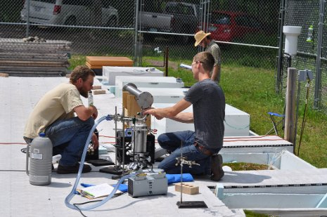 Evan Kane, left, works on a peatcosm with one of his fellow researchers. (Credit: Michigan Technological University)