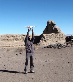 A researcher holds the drone in the middle of a survey area. (Credit: César Parcero-Oubiña)
