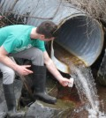 Shane DeGaetano, a senior in Biological and Environmental Engineering at Cornell University, collects storm water near Cascadilla Creek in Ithaca, New York. The water was analyzed for chloride associated with road salt. (Credit: Lauren McPhillips)