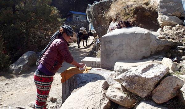 Sherpa woman washing cloths using a town water supply near Lausasa township. (Credit: Kirsten Nicholson)