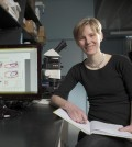 niche in ecosystem / Co-author and UW biology professor Heidi Swanson sits next to charts generated by the nicheROVER tool. (Courtesy of Martin Schwalbe)