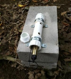 A Solinst Barologger Edge Barometric Pressure Logger is mounted on a cinder block. (Credit: Jessica Schuster)