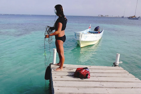 Madz Negro uses a hydrophone and digital recorder to capture sounds from and around Panamanian coral reefs. (Credit: Illinois Wesleyan University)