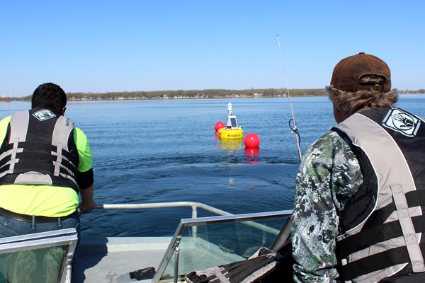 Members of the Iowa Lakeside Laboratory help deploy a new data buoy in West Okoboji Lake. (Credit: Doug Nguyen / NexSens Technology)