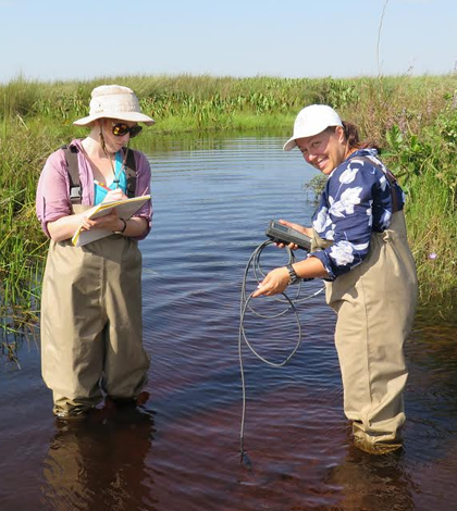 Suzanne Gray (right) and Tiffany Atkinson, a student, collect environmental data with a YSI Pro2030 in a swamp in western Uganda. (Credit: Ohio State University)