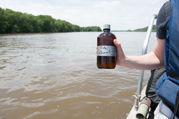 A LACMRERS student takes a water sample from a side channel of the Mississippi River. (Credit: University of Iowa)
