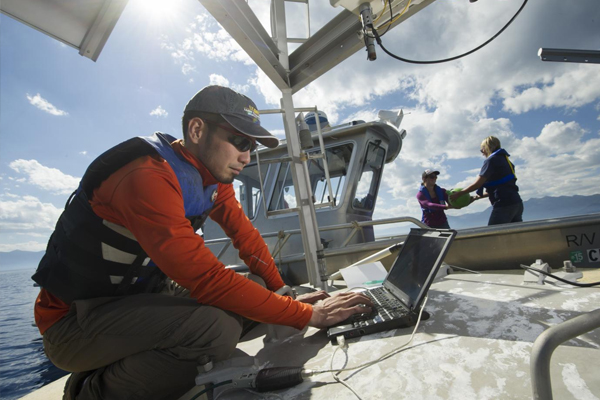 UC Davis researcher Shohei Wantanabe gathers data from a NASA Jet Propulsion Lab research buoy. (Credit: UC Davis)