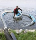 Jon Bunn prepares a floating suction hose to vacuum algae from the bay. (Credit: C.T. Kruger)
