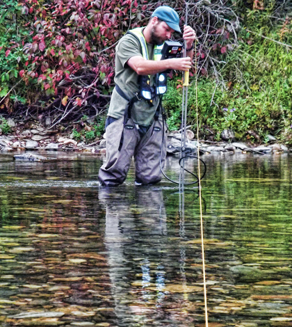 A hydrologic technician from the USGS Idaho Water Science Center measures streamflow in the St. Joe River at Red Ives Ranger Station in northern Idaho. (Credit: Dan Hess / U.S. Geological Survey)