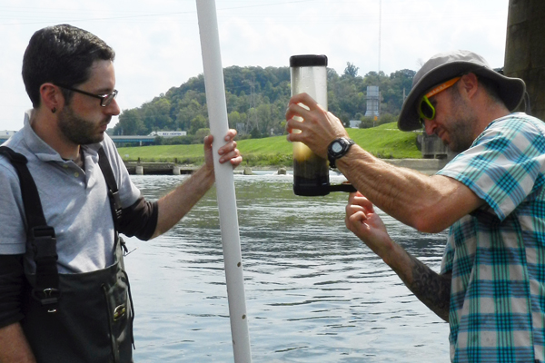 Daniel Hoffman (left) watches as Lee Slone secures the bottom of a sediment core with electrical tape on the downstream side of a dam on the Lower Great Miami River. (Credit: Nate Christopher / Fondriest Environmental)