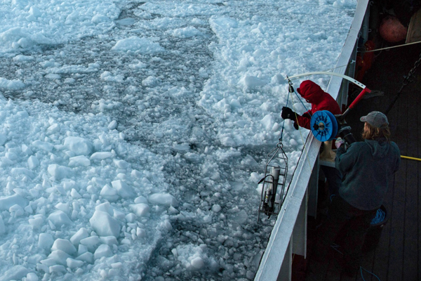 Researchers race to retrieve equipment as sloughed-off glacial ice threatens to trap their boat. (Credit: University of California, Irvine)