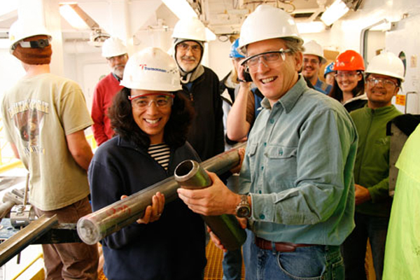 Christina Ravelo (Co-Chief Scientist, University of California, Santa Cruz) and Alan Mix (Stratigraphic Correlator, Oregon State University) show off the core section that broke a depth record of 458.4 meters below the seafloor. (Credit: Carlos Alvarez Zarikian / Integrated Ocean Drilling Program)