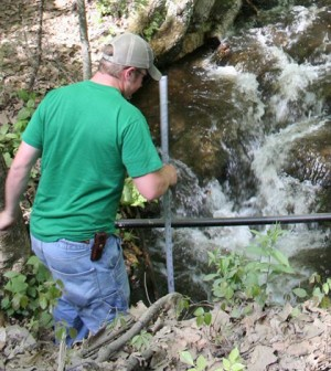 Tyler Evans measuring depth at a custom tag antenna site for estimating discharge at Mitchell Brook, Whately, Massachusetts. (Credit: U.S. Geological Survey)
