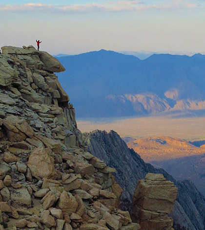 A Stanford University researcher stands on a peak in the Sierra Nevada mountain range. New evidence shows the California mountain range is 40 million years old, much older than previously thought. (Credit: Hari Mix / Stanford University)