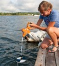Volunteer Michelle Helms measures water clarity using a Secchi disk in Apponagansett Bay. (Credit: Buzzards Bay Coalition)