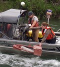 Hydrologic technicians retrieve a bedload sample from the Kootenai River near Bonners Ferry, Idaho. The U.S. Geological Survey compared the results of bedload and suspended sediment sampling with data collected from acoustic devices submerged in the river. (Credit: U.S. Geological Survey)