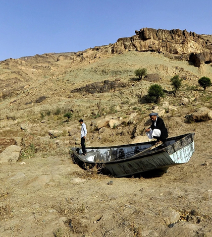 Two men inspect an abandoned boat in Yemen, one of the countries most affected by the scarcity of freshwater. (Credit: Yahya Arhab / EPA)