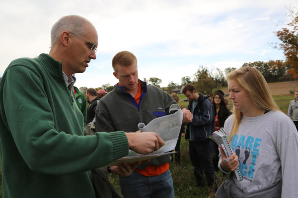 Richard Crago (left) reviews a map with Bucknell University students. (Credit: Bucknell University)