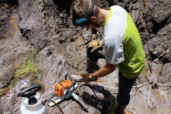 Lead author Brendan Murphy preparing to drill samples of bedrock from the streambed of Puanui Gulch on the dry side of Kohala Peninsula. (Credit: Kory Kirchner)