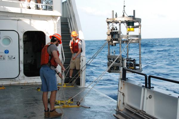 Ryan Holmes, foreground, readies a sensor deployment. (Credit: Jim Moum / Oregon State University)