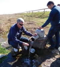 Mark Anderson, director of the USGS South Dakota Water Science Center, demonstrates how to collect a stable isotope sample from a flowing well near Sis, Armenia. (Credit: U.S. Geological Survey)