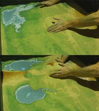 Researchers show off the augmented reality sandbox. (Credit: University of California, Davis)